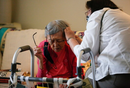 Sakaguchi helps mother Sakaguchi, 94, with her hearing aid at Nikkei Manor, an assisted living facility in Seattle