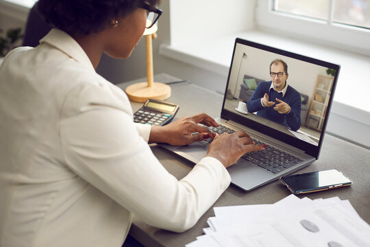 Young employee having online work meeting with senior boss, over shoulder view. Two multiethnic business people discussing current project via video call. Virtual communication and remote job concept