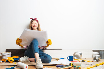 Obraz Happy girl sitting on floor with blueprint - fototapety do salonu