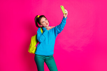 Photo of pretty charming young woman dressed blue hoodie backpack self kiss video modern gadget isolated pink color background