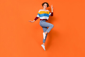 Photo of charming pretty young woman wear striped sweater showing v-sign jumping high isolated...