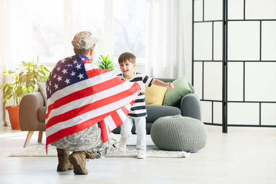 Little boy meeting his military father at home. Memorial Day celebration