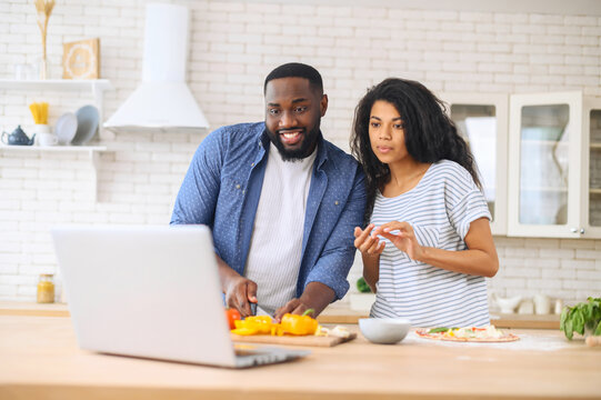 Interested young mixed-race couple attentively watching online cooking classes, learning how to make dinner lunch pizza, watching video blog course from laptop in the kitchen, preparing vegetables