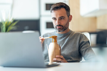 Handsome mature business man eating take away noodles while working with laptop at home.