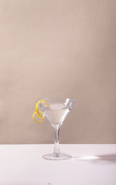 Glass of lemon drop martini cocktail on table against grey background