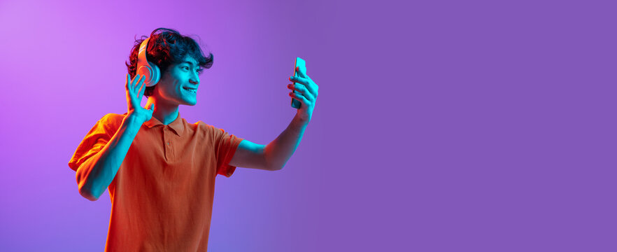 Young man talking on phone isolated over pink purple background in neon light