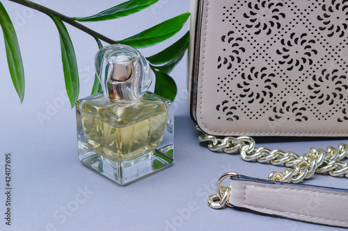 On a gray background, items for a feminine evening look - women's perfume and a beige clutch bag on a gold metal chain. Possible gift ideas for Christmas, Valentine's Day, Women's Day, Mother's Day.