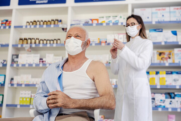 Therapy in a nursing home pharmacy. Female pharmacist gives therapy to a senior man who is sitting on a chair and has taken off his shirt. Vaccination, corona virus breaking news