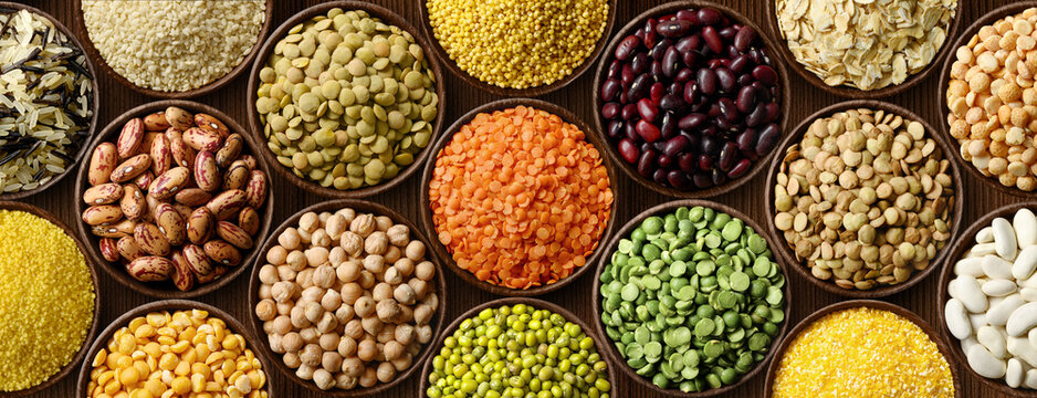 Various colorful legumes and cereals in bowls background.