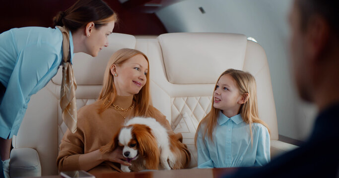 Flight attendant taking order from family in first class airplane interior