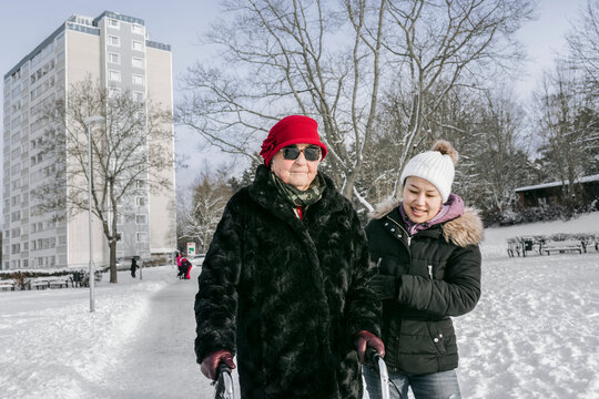 Senior woman with female home caregiver walking at winter
