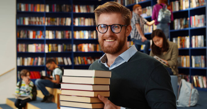 Bearded school teacher or librarian holding books in hands standing in library interior.
