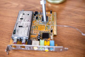 Lutowanie cyną na płytce drukowanej. Naprawa podzespołów komputerowych. Czynności, które wykonują serwisy komputerowe. - fototapety na wymiar