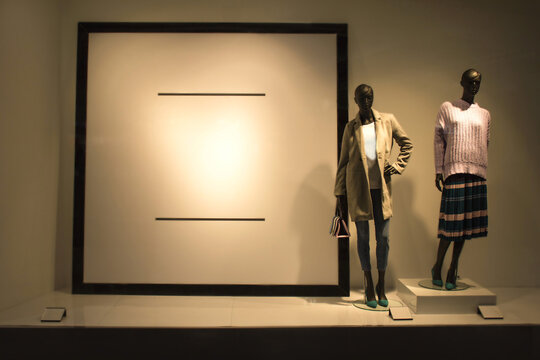 Ukraine, Kherson - January 31, 2020: Two female mannequins in a shop window near blank stand. Place for text. Black dummies wear spring autumn or winter collection clothes. Black Friday