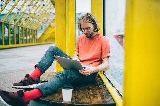 Casual hipster man working on startup in pedestrian bridge