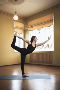 A woman in black sportswear practicing yoga performs the natarajasana exercise, the pose of the king of dancers. A model is exercising in a room on a mat