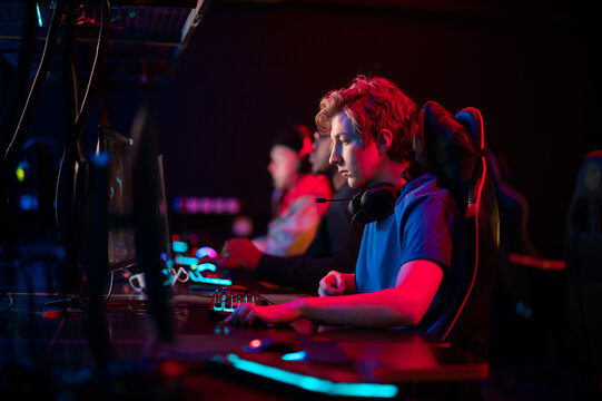 Training bootcamp for professional esports players. Young cyber-athletes play an online shooter game. Glowing keyboard, neon light.