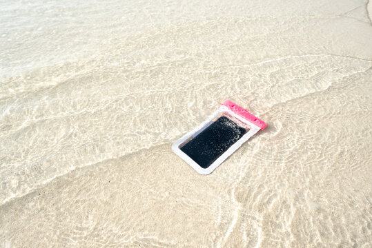 Waterproof case on a smartphone, phone for taking pictures under water. Phone in the waterproof case underwater, on the sands