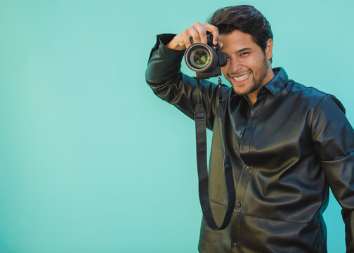 Young Latino man holds a camera on an Aztec green background with copy space. Focus on the face
