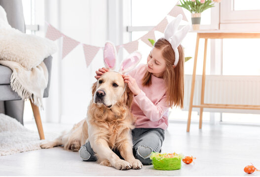 Little girl with golden retriever dog at Easter