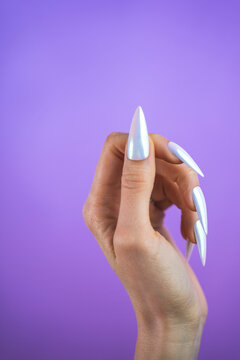 Pearlescent unicorn design manicure press-on nails isolated against a purple background