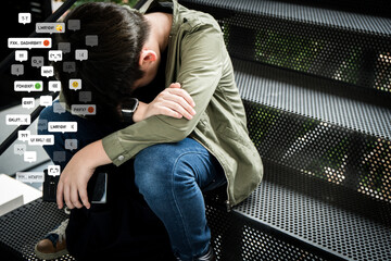 Cyberbullying - social media harassment concept. An asian preteen, teenager boy sitting alone hold...
