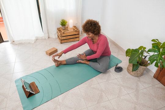 African senior woman doing online yoga class at home - Healthy lifestyle and joyful elderly concept - Focus on face