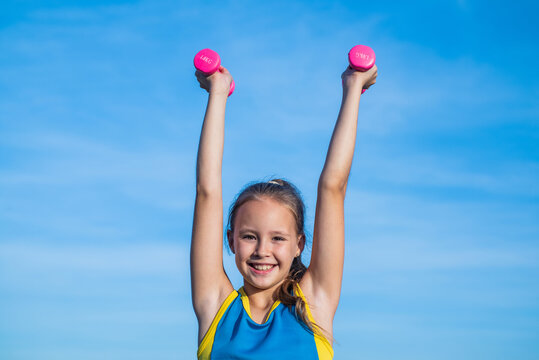 aim and success. healthy child training with barbells. fitness kid hold dumbbell. weight lifting. teenage girl do exercise. happy childhood. future of sport. warm up for workout in morning