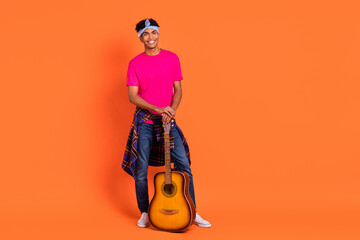 Full length body size photo young guy smiling in stylish outfit keeping guitar isolated bright...