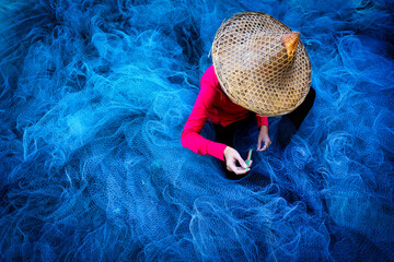 Women fisherman hands sewing blue fishing nets sitting on the ground and surrounded big net