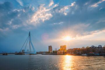 Rotterdam skyline cityscape with Erasmusbrug bridge over Nieuwe Maas in contre-jur on sunse, Netherlands.