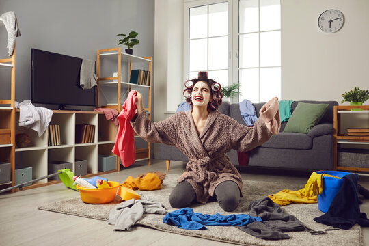 Exhausted young woman cleaning her house. Desperate tired busy housewife in hair curlers and face mask picking up scattered clothes from floor, crying and complaining about terrible mess at home