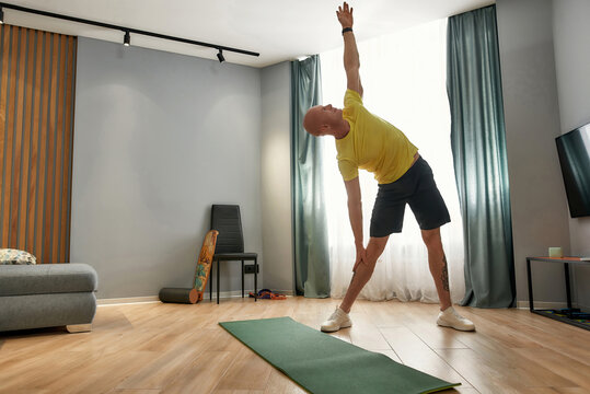 Full length shot of male coach having fitness training, working out in living room at home on a daytime