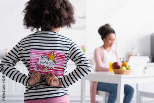 back view of african american child holding happy mothers day card near mom working in kitchen on blurred background