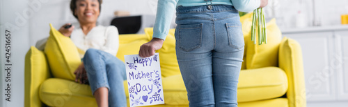 back view of african american child with happy mothers day card near happy mom on blurred background, banner
