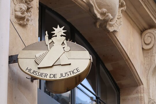 Plaque officielle d'un huissier de justice français sur la façade d'un immeuble, à Paris – mars 2021 (France)