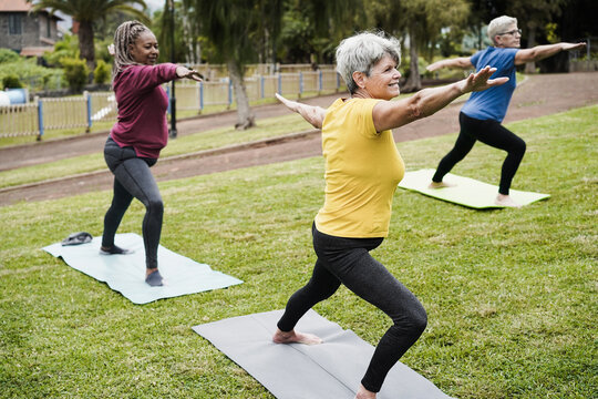 Senior people doing yoga class outdoor at city park - Focus on center woman face