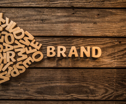 """Make your own brand. The word """"Brand"""" is lined with wooden letters on wood planks of table. Photo image"""