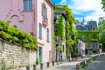 Montmartre in Paris, a very romantic parisian street and houses, with the basilica Sacre-Coeur in background