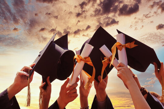 International students in mortar boards and bachelor gowns with diplomas.