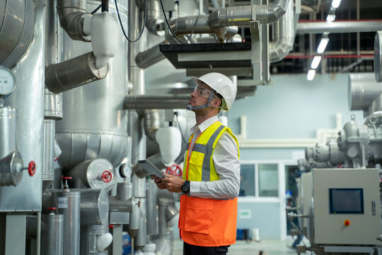 Engineer checking and maintenance technical data of system equipment condenser Water pump and piping air compressor system at manufacturing factory.