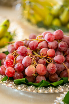 Plate of red grapes in a cluster on a table being catered for a wedding ceremony