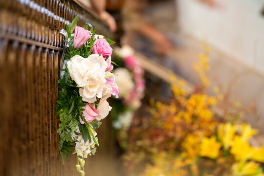 Bouquet of pink and white roses place on a railing for a wedding ceremony