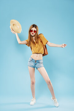 Pretty woman in hat fashionable clothes backpack posing blue background