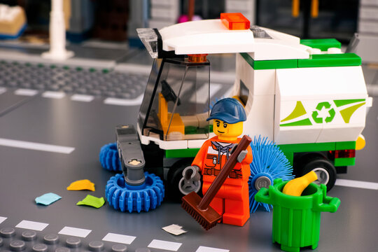 Tambov, Russian Federation - January 17, 2020 Lego cleaner minifigure with brush cleaning street near street sweeper truck. Studio shot.