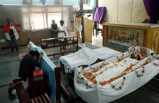 A woman prays inside a church on Good Friday, in Mumbai