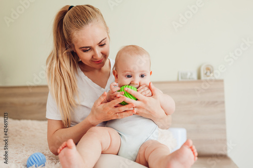 Mother's day. Young woman playing with her newborn baby son at home. Family having fun. Infant biting ball on bed