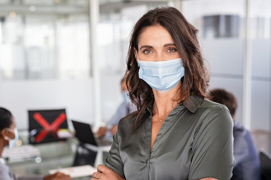 Mature business woman wearing surgical mask at work