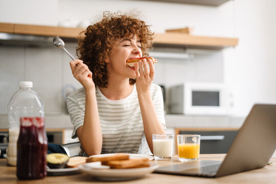 Smiling young woman using laptop while having breakfast at home kitchen