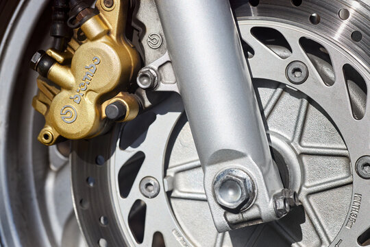 Berlin - April 2021: Front disc brakes BREMBO of race bike Honda closeup. Front radial mount caliper sport bike, Motorcycle with Twin Floating Disk Brake and ABS system with copyspace